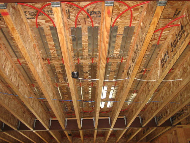 Janes radiant install radiant floor heating yourself tubing is stapled to the bottom of the subfloor between the joists using aluminum heat transfer plates the plates add to the efficiency and response of the solutioingenieria Choice Image